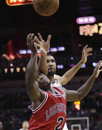 San Antonio Spurs' Tim Duncan, top, reaches over Chicago Bulls' Nate Robinson (2) for a loose ball during the first half of an NBA basketball game on Wednesday, March 6, 2013, in San Antonio. (AP Photo/Eric Gay)