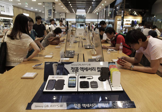 Shoppers try out Samsung Electronics' Galaxy S III smartphones at a showroom in Seoul, South Korea, Friday, July 27, 2012. Samsung, the world's largest technology company by revenue, reported another record-high quarterly profit as customers flocked to Galaxy smartphones, helping it outdo rivals at a challenging time for the global tech industry. Samsung Electronics Co.'s net profit swelled to 5.2 trillion won ($4.5 billion) in the April-June quarter, a 48 percent jump from a year earlier. (AP Photo/Ahn Young-joon)