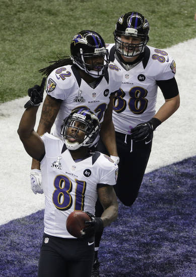 Baltimore Ravens wide receiver Anquan Boldin (81) celebrates his 13-yard touchdown reception against the San Francisco 49ers  as teammates Torrey Smith and Dennis Pitta follow during the first half of the NFL Super Bowl XLVII football game, Sunday, Feb. 3, 2013, in New Orleans. (AP Photo/Charlie Riedel)
