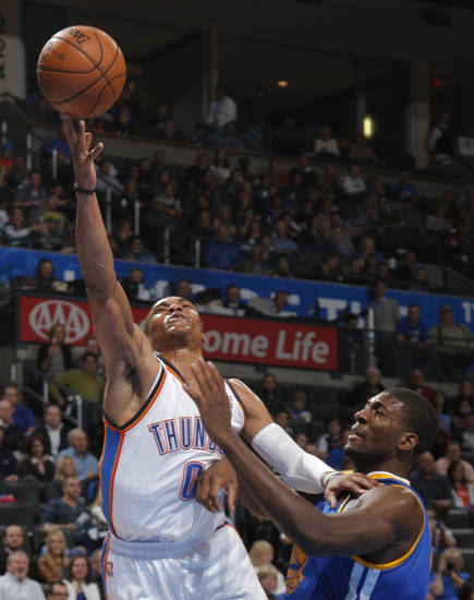 Oklahoma City 's Russell Westbrook (0) takes a shot over Golden State's Festus Ezeli (31) during an NBA basketball game between the Oklahoma City Thunder and the Golden State Warriors at Chesapeake Energy Arena in Oklahoma City, Sunday, Nov. 18, 2012.  Photo by Garett Fisbeck, The Oklahoman