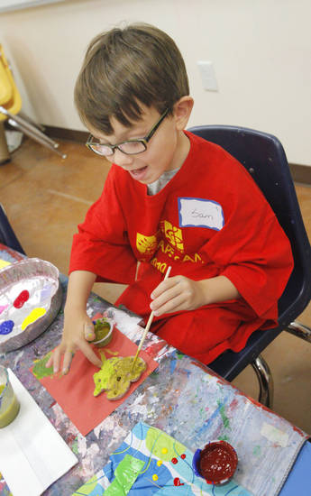 Sam Ray, 5, paints his clay sea creature.
