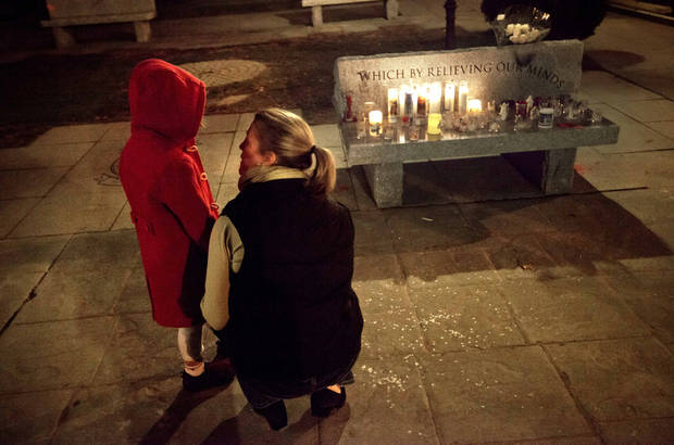 Rhonda Eleish, right, talks to her daughter Kari Ergmann, 6, both of Bridgewater, Conn., next to a candlelight vigil outside the Edmond Town Hall, Saturday, Dec. 15, 2012, in Newtown, Conn. Eleish suspects her daughter knew one of the victims of Friday's shooting at Sandy Hook Elementary School in Newtown that killed 26 people, including 20 children. (AP Photo/David Goldman) ORG XMIT: CTDG149