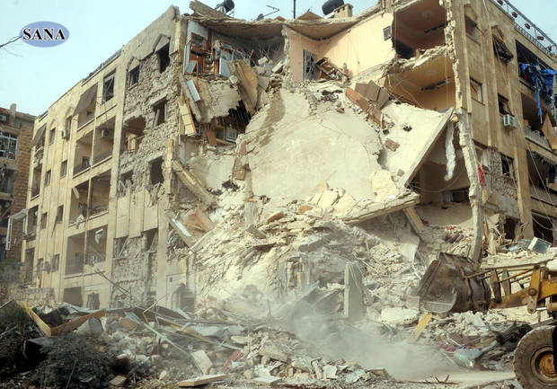 This photo released by the Syrian official news agency SANA, shows damage after a rocket slammed into a building, killing at least 12 people, in Aleppo, Syria, Friday, Jan. 18, 2013. In a spike in civil war violence that Syrian state media blamed on rebel fighters a rocket attack in the northern city of Aleppo occurred during a particularly bloody week nearly two years after an uprising began against Assad's regime. (AP Photo/SANA)