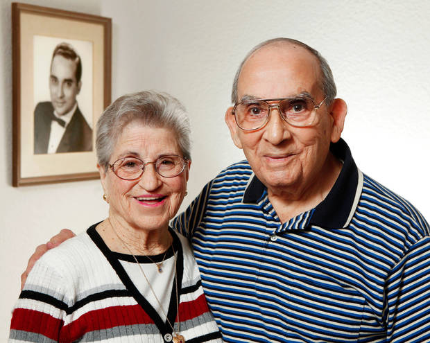 "Miguelito and Olga Miranda married five months ago and are beginning a life together as husband and wife after a nearly 70 year separation.  Miguelito and Olga were neighbors in Puerto Rico and childhood sweethearts, described by both as the other's ""first love.'   Both married other people and their lives took them in different directions; Olga married a serviceman and  came to America while Miguelito married a woman and became a famous  band leader of a Latin orchestra,  In later years, their spouses died, leaving them both alone and lonely.  Miguelioto began a search to find his first love and he proposed to her on her 90th birthday.  The couple was married in September, 2011. They are photographed in the bedroom of their home in Del City on Monday, Feb. 13, 2012.  The picture hanging on the wall is a portrait of Miguelito made in his younger years as a band leader. 
