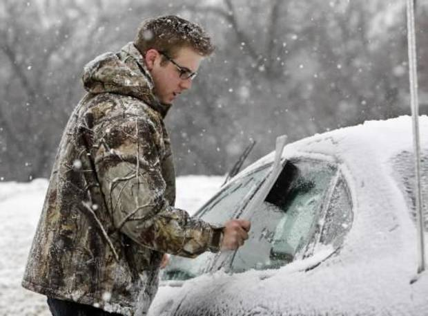 Michael Frazer clears the ice off of his car as he prepares to go to work in Edmond, OK, Friday, Jan. 29, 2010. By Paul Hellstern