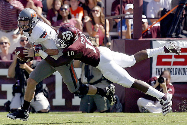Oklahoma State&#039;s Brandon Weeden is sacked by Texas A&amp;M&#039;s Sean Porter in the first half Saturday in College Station, Texas. Photo by Sarah Phipps, The Oklahoman 