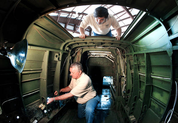 Bill Hayes works inside an A-26 at Guthrie Municipal Airport. Looking through the hatch is James Dudnelly Jr.  Photo by Jim Beckel, The Oklahoman