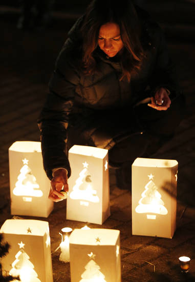 Tracy Tarantino places a candle on a makeshift memorial near the elementary school where a day earlier a gunman opened fire, Saturday, Dec. 15, 2012, in Newtown, Conn. The man, who died from a self-inflicted wound, allegedly killed his mother at their home and then opened fire Friday inside the Sandy Hook Elementary school, massacring 26 people, including 20 children. (AP Photo/Julio Cortez) ORG XMIT: CTJC141