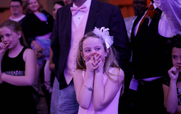 A girl laughs as dads are selected for a dance contest. Midwest City Parks and Recreation Department hosted the city's annual Daddy-Daughter Dance that featured three 90-minute dance sessions at the Reed Center on Saturday, Feb. 16, 2013.    Photo by Jim Beckel, The Oklahoman