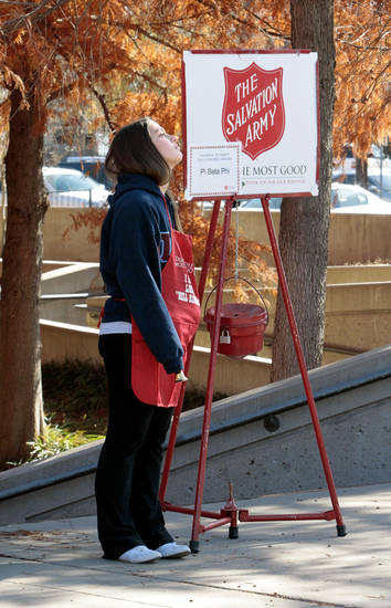 Above and right: Salvation Army bell ringer Jenna Geresi, of Norman, rings a bell and mans a kettle for her sorority Pi Beta Phi on the campus of the University of Oklahoma. Photos by Steve Sisney, The Oklahoman
