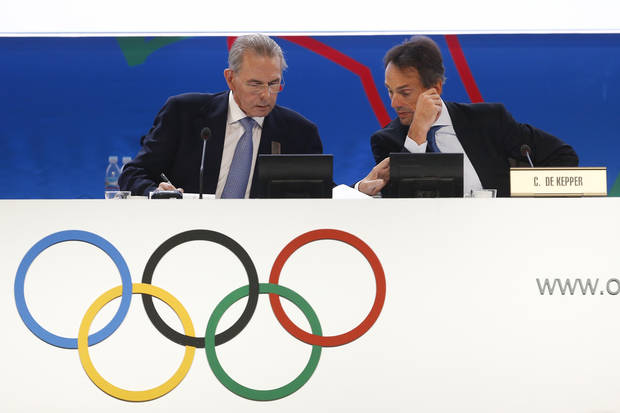 Jacques Rogge, president of the International Olympic Committee (IOC), left, talks to Christophe De Kepper, IOC director general, right, during a report session during the 125th IOC session in Buenos Aires, Argentina,  Monday, Sept. 9, 2013. (AP Photo/Victor R. Caivano)