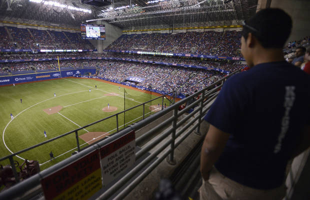 A fan watches as the San Diego Padres and the Texas Rangers play an exhibition baseball game, Saturday, March 30, 2013, at the Alamodome in San Antonio. Texas won 5-2. (AP Photo/Darren Abate)