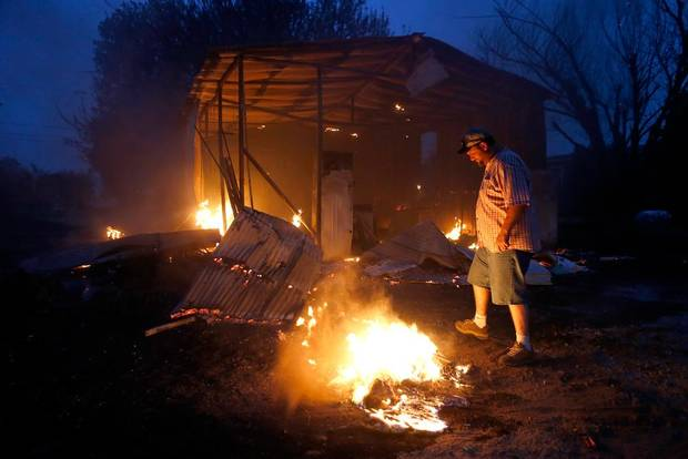Phillip Green tries to put out hot spots near his burned storage building next to his home in Luther, Okla., after wildfire moved through the area on Friday, August 3, 2012. Photo by Bryan Terry, The Oklahoman