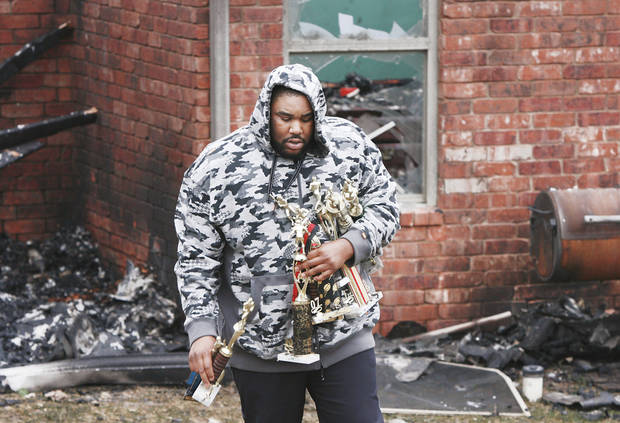A man carries trophies from the burned house of Nathan and Sammetra Christmon as he helps salvage personal belongings from the home at 2040 Westbury St. in the Oakwood East Royale neighborhood in Midwest City. Photo by JIM BECKEL, THE OKLAHOMAN