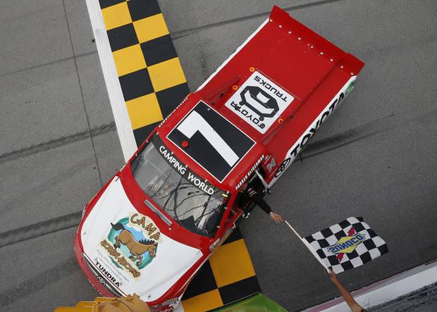 Parker Kligerman is handed the checkered flag after winning the NASCAR Camping World Truck Series race at Talladega Superspeedway in Talladega, Ala., Saturday, Oct. 6, 2012. (AP Photo/Tom Pennington, Pool_
