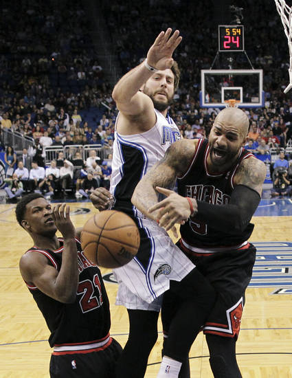 Chicago Bulls' Jimmy Butler (21) and Carlos Boozer, right, battle for a rebound against Orlando Magic's Josh McRoberts, center, during the first half of an NBA basketball game, Wednesday, Jan. 2, 2013, in Orlando, Fla. (AP Photo/John Raoux)