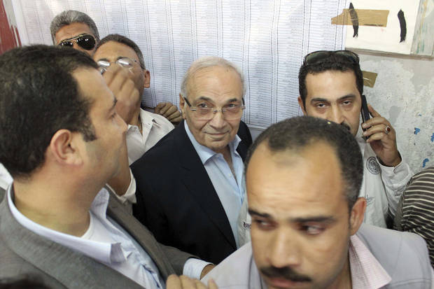 "Egyptian presidential candidate Ahmed Shafiq, center, arrives to vote at a polling site in Cairo, Egypt, Wednesday, May 23, 2012. Presidential Candidate and former Egyptian Prime Minister Ahmed Shafiq was met by scores of protesters as he arrived to cast his vote on Wednesday. Shafiq arrived to vote in an upscale neighborhood east of Cairo to protesters yelling ""down with the feloul"" or ""remnants"" of the regime. (AP Photo) ORG XMIT: CAI125"