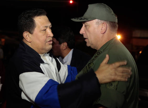 In this photo released by Miraflores Press Office, Venezuela's President Hugo Chavez, left, speaks with his Defense Minister Diego Molero upon his arrival to Simon Bolivar airport in Maiquetia, near Caracas. Venezuela, Friday, Dec. 7, 2012. Chavez arrived back home in Caracas after 10 days of medical treatment in Cuba. (AP Photo/Miraflores Press Office, Marcelo Garcia)