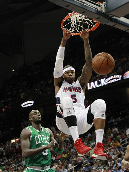 Atlanta Hawks forward Josh Smith (5) scores as Boston Celtics forward Kevin Garnett (5) watches during the first half of Game 2 of an NBA basketball first-round playoff series Tuesday, May 1, 2012, in Atlanta. (AP Photo/John Bazemore)