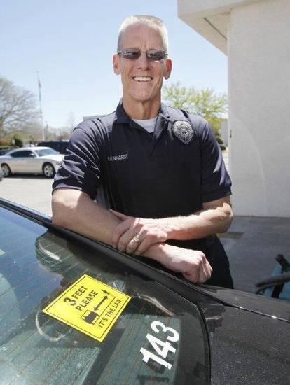 Edmond police Lt. Chuck Linhardt stands by a bumper sticker reminding drivers to stay three feet away from bicylists. PHOTO BYPAUL HELLSTERN, THE OKLAHOMAN <strong>PAUL HELLSTERN - THE OKLAHOMAN</strong>