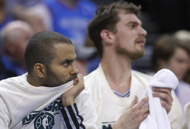 San Antonio Spurs guard Tony Parker, left, and center Tiago Splitter, right, watch from the bench in the second quarter of an NBA basketball game against the Oklahoma City Thunder in Oklahoma City, Thursday, April 4, 2013. Oklahoma City Thunder won 100-88. (AP Photo/Sue Ogrocki)