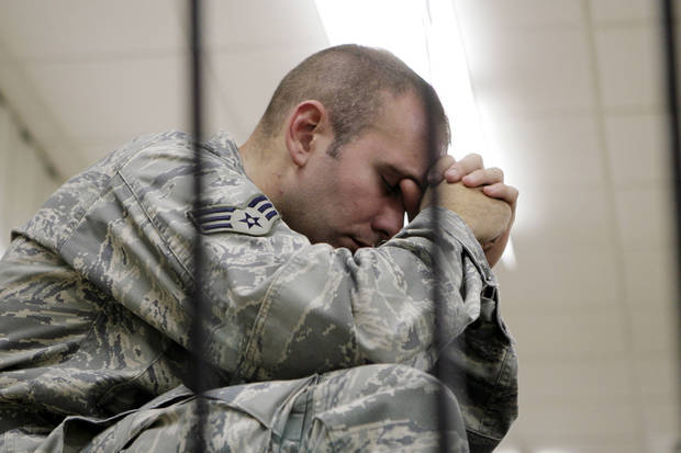 In this photo taken on Aug. 30, 2009, Senior Airman Shaun Thomas, of the 335th Fighter Squadron at Seymour Johnson Air Force Base in Goldsboro, N.C., spends a few moments alone shortly before deploying to Afghanistan.  (AP Photo/News-Argus, Greg Sousa)