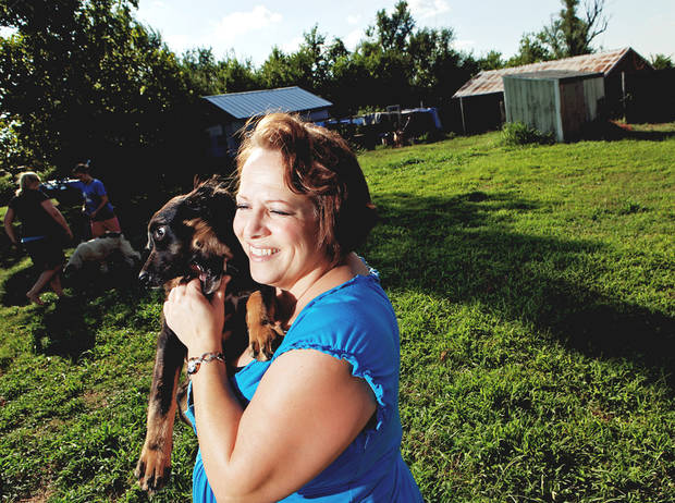 Heather McDaniel, director of Must Love Dogs Rescue, holds one of the dogs up for adoption at her rescue near Harrah. Photo BY  JOHN CLANTON,  THE OKLAHOMAN