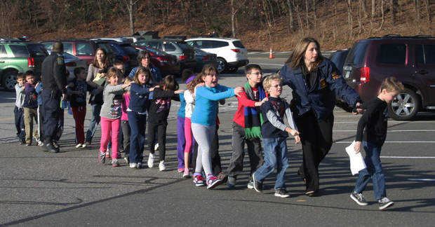 In this photo provided by the Newtown Bee, Connecticut State Police lead a line of children from the Sandy Hook Elementary School in Newtown, Conn. on Friday, Dec. 14, 2012 after a shooting at the school. (AP Photo/Newtown Bee, Shannon Hicks) MANDATORY CREDIT: NEWTOWN BEE, SHANNON HICKS
