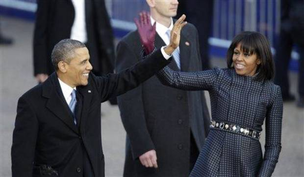 President Barack Obama and first lady Michelle Obama wave as they arrive in front of the White House during the Inaugural parade in Washington, Monday, Jan. 21, 2013.  Thousands marched during the 57th presidential inauguration parade after the ceremonial swearing-in of Obama. (AP Photo/Gerald Herbert)