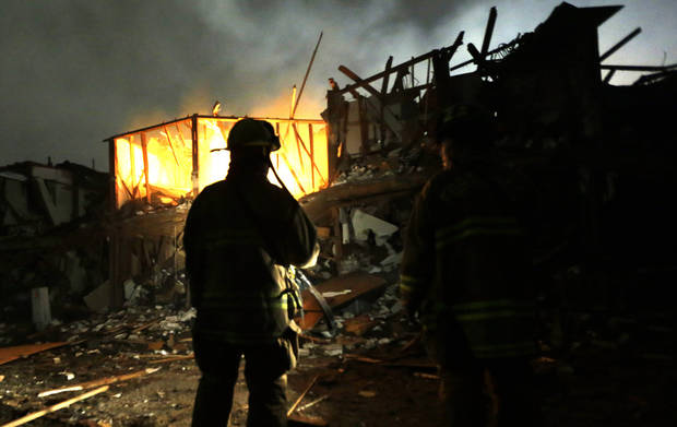 Firefighters use flashlights to search a destroyed apartment complex near a fertilizer plant that exploded earlier in West, Texas, in this photo made early Thursday morning, April 18, 2013.  (AP Photo/LM Otero)