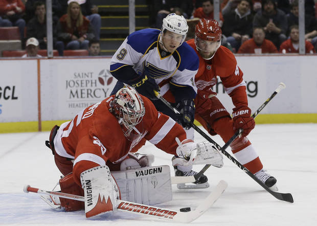 Detroit Red Wings goalie Jimmy Howard (35) reaches for the puck in front of St. Louis Blues center Jaden Schwartz (9) and Red Wings defenseman Jakub Kindl (4), of the Czech Republic, during the first period of an NHL hockey game in Detroit, Friday, Feb. 1, 2013. (AP Photo/Carlos Osorio)