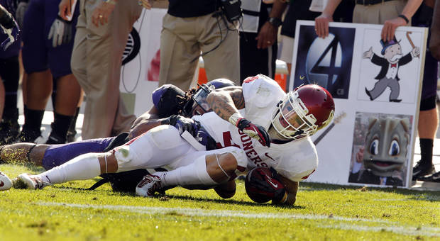 Oklahoma's Kenny Stills (4) catches a pass and is tackled by TCU's Jason Verrett (2) during the second half of the college football game where the University of Oklahoma Sooners (OU) defeated the Texas Christian University Horned Frogs (TCU) 24-17 at Amon G. Carter Stadium in Fort Worth, Texas, on Saturday, Dec. 1, 2012. The figures at right are defensive plays.  Photo by Steve Sisney, The Oklahoman