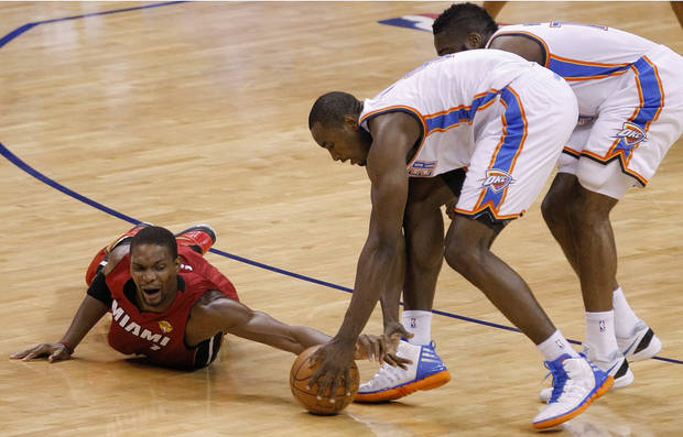 Miami's Chris Bosh (1) dives for the ball beside Oklahoma City's Serge Ibaka, center, and Oklahoma City's James Harden during Game 1 of the NBA Finals between the Oklahoma City Thunder and the Miami Heat at Chesapeake Energy Arena in Oklahoma City, Tuesday, June 12, 2012. Photo by Sarah Phipps, The Oklahoman