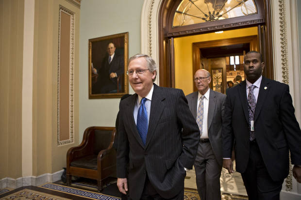"Senate Minority Leader Mitch McConnell, R-Ky., followed by Sen. Pat Roberts, R-Kan., second from right, leaves the Senate chamber to meet with fellow Republicans  in a closed-door session as the ""fiscal cliff"" negotiations continue at the Capitol in Washington, Sunday, Dec. 30, 2012.  Leaders in the Senate and the House are under pressure to find a legislative path to head off the automatic tax hikes and spending cuts set to take effect Jan. 1, 2013. (AP Photo/J. Scott Applewhite)"