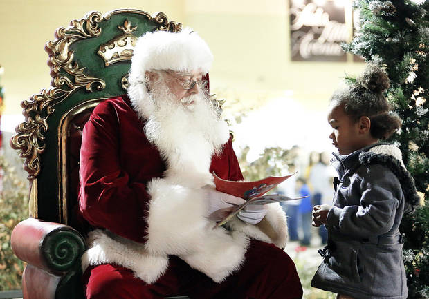 Santa talks with Narilyn Wooden, 4, on Tuesday during a tree-lighting ceremony at The Outlet Shoppes at Oklahoma City. PHOTOS BY SARAH PHIPPS, THE OKLAHOMAN