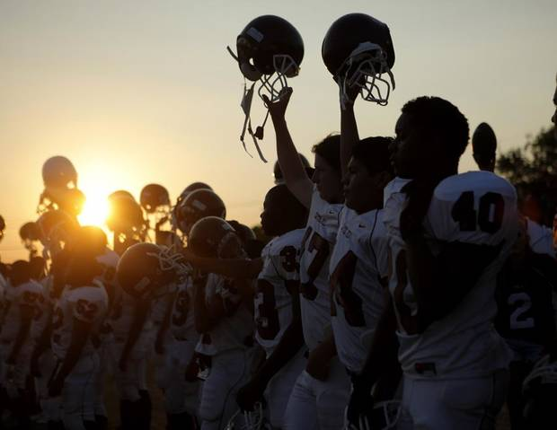 The Capitol Hill football team lifts their helmets during the kickoff of a football game against Oklahoma Centennial at Star Spencer in Oklahoma CIty, Thursday, September 1, 2011. Photo by Bryan Terry, The Oklahoman ORG XMIT: KOD