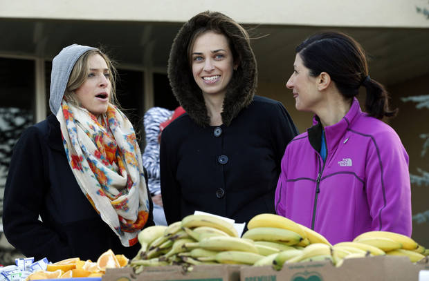 Junior League members Lane Krattiger, Lauren Cornwell and Lisa Robertson are dressed for the cold as they help pass out bananas and fruit during the annual Monster Dash on Saturday, Nov. 3, 2012.  Photo by Steve Sisney, The Oklahoman