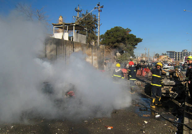 Iraqi firefighters distinguish a fire at the scene of a bomb attack in Kirkuk, 180 miles (290 kilometers) north of Baghdad, Iraq, Sunday, Feb. 3, 2013. A suicide car bomber joined by other suicide attackers on foot assaulted a provincial police headquarters in a disputed northern Iraqi city killing and wounding scores of people, police said. (AP Photo/Emad Matti)