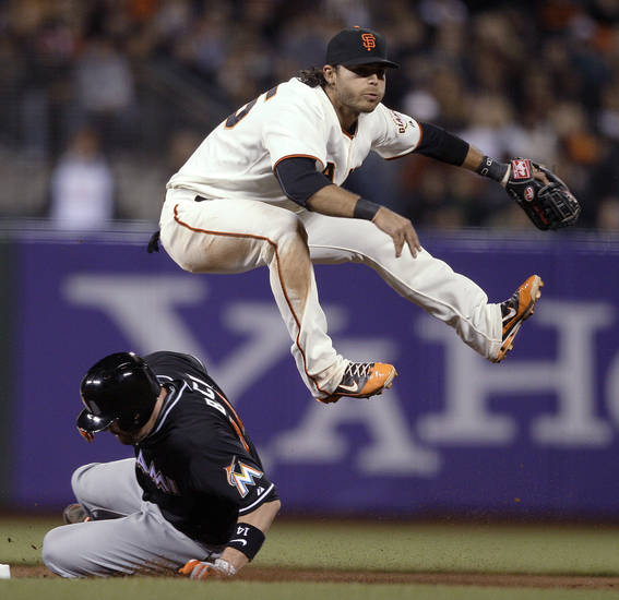 San Francisco Giants shortstop Brandon Crawford leaps over Miami Marlins'John Buck while turning a double play on Carlos Zambrano's ground ball during the fourth inning of a baseball game in San Francisco, Wednesday, May 2, 2012. (AP Photo/Jeff Chiu)