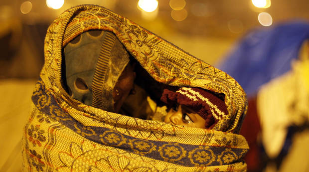 A woman laborer wraps herself and her child in a shawl to protect themselves from the cold at the Sangam, the confluence of rivers Ganges, Yamuna and the mythical Saraswati in Allahabad, India, Friday, Dec. 28, 2012. North India continues to face extreme weather conditions with dense fog affecting flights and trains and cold wave conditions claiming more than 50 lives, according to local reports. (AP Photo/Rajesh Kumar Singh)
