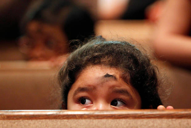 Pre-kindergartner Julianna Garcia kneels down during Ash Wednesday Mass at Corpus Christi Catholic Church on Wednesday, Feb. 22, 2012, in Houston. (AP Photo/Houston Chronicle, Mayra Beltran)  MANDATORY CREDIT
