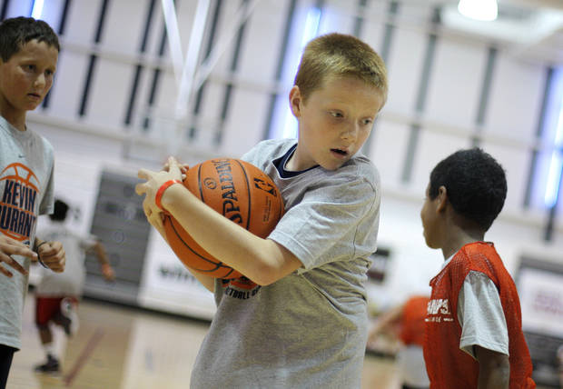 Gavin Pendergraff, 10 of Bartlesville, steals the ball from Keshon Williams, 9 of Guymon, during the Kevin Durant basketball camp at Heritage Hall Wednesday, June 29, 2011.  Photo by Garett Fisbeck, The Oklahoman