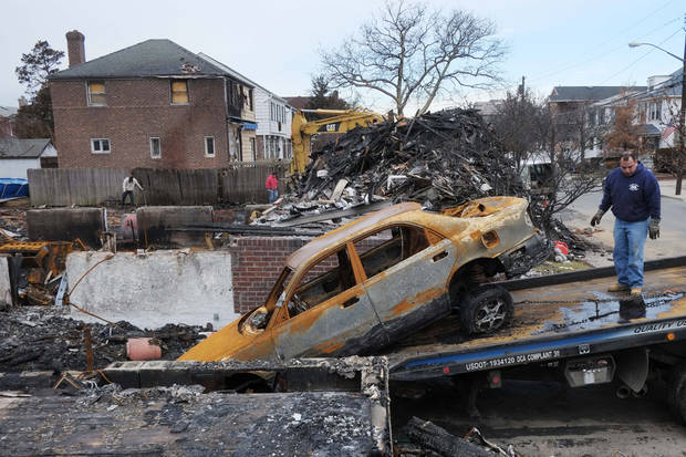 A tow truck driver prepares to remove the shell of an incinerated car from the wreckage of a home in the Belle Harbor section of New York, Thursday, Dec. 20, 2012. The car and a dozen homes were burned during  a fire that swept through the neighborhood during Superstorm Sandy on Oct. 29, 2012. (AP Photo/Mark Lennihan)