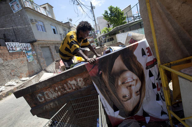 A man collects paper in a garbage container during municipal elections in the Complexo da Mare slum in Rio de Janeiro, Brazil, Sunday, Oct. 7, 2012. Voters across Latin America's biggest country are electing mayors and municipal council members. (AP Photo/Silvia Izquierdo)
