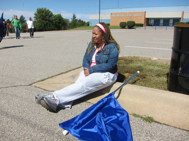 Class of 1996 graduate Amber Mansfield, 35, rests for a minute during Millwood High School marching band practice Saturday at the school, 6724 N Martin Luther King Avenue. Mansfield, of Spencer, was a flag girl and played the clarinet as a Millwood band member. <strong>Carla Hinton - The Oklahoman</strong>