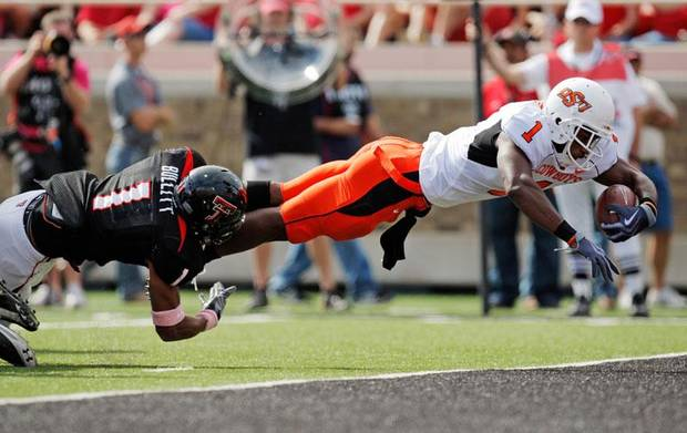 OSU's Joseph Randle (1) dives for a touchdown as Terrance Bullitt (1) of Texas Tech defends in the first quarter during the college football game between the Oklahoma State University Cowboys and Texas Tech University Red Raiders at Jones AT&T Stadium in Lubbock, Texas, Saturday, October 16, 2010. Photo by Nate Billings, The Oklahoman