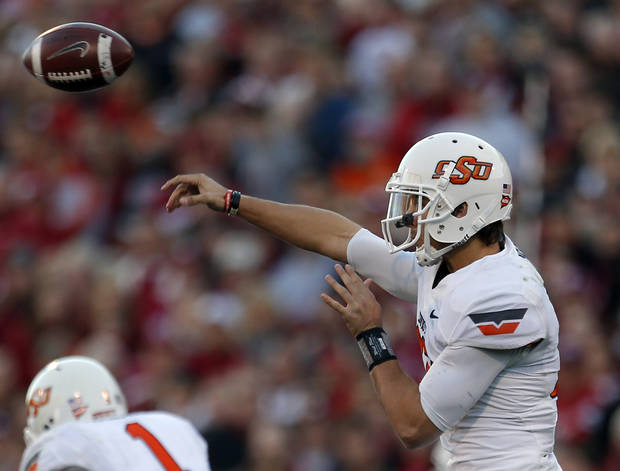 Oklahoma State's Clint Chelf (10) throw the ball during the Bedlam college football game between the University of Oklahoma Sooners (OU) and the Oklahoma State University Cowboys (OSU) at Gaylord Family-Oklahoma Memorial Stadium in Norman, Okla., Saturday, Nov. 24, 2012. OU won 51-48 in overtime. Photo by Sarah Phipps, The Oklahoman