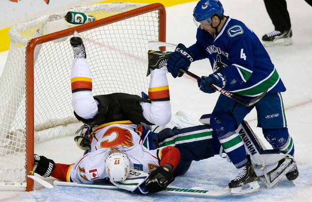 Calgary Flames&#039; Blake Comeau, left, crashes into Vancouver Canucks goalie Cory Schneider as Canucks&#039; Keith Ballard, right, watches during the second period an NHL hockey game game in Vancouver, British Columbia, on Wednesday, Jan. 23, 2013. (AP Photo/The Canadian Press, Darryl Dyck)