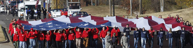 The city of Midwest City teamed with civic leaders and local merchants to display their appreciation for veterans and active military forces by staging a hour-long Veteran's Day parade that stretched more than a mile and a half along three of the city's busiest streets Monday morning, Nov. 12, 2012. Hundreds of people lined the parade route, many of them waving small American flags that had ben distributed by volunteers who marched near the front of the parade. A fly-over performed by F-16s from the138th Fighter Wing, Oklahoma Air National Guard unit in Tulsa thrilled spectators. Five veterans representing military personnel who served in five wars and military actions served as  Grand Marshals for the parade. Leading the parade was the Naval Reserve seven-story American flag, carried by 100 volunteers from First National Bank of Midwest City, Advantage Bank and the Tinker Federal Credit Union. The flag is 50 feet by 76 feet, weighs 110 pounds and was sponsored by the MWC Chapter of Disabled American Veterans. Photo by Jim Beckel, The Oklahoman