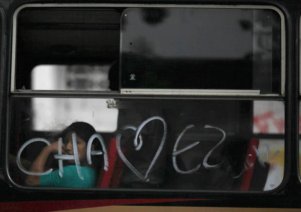 A woman looks out a bus window spray painted with the last name of Venezuela's President Hugo Chavez, in Caracas, Venezuela, Friday, Oct. 5, 2012. Venezuelans head to the polls Sunday to vote in their country's presidential election, deciding between Chavez and opposition candidate Henrique Capriles. (AP Photo/Ariana Cubillos)